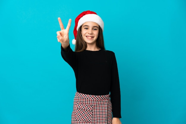 Klein meisje met kerstmuts geïsoleerd op blauwe achtergrond glimlachend en overwinning teken tonen