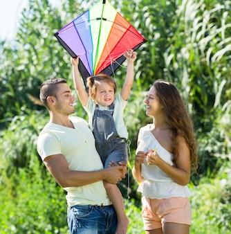 Klein meisje met kite zittend op vaders armen