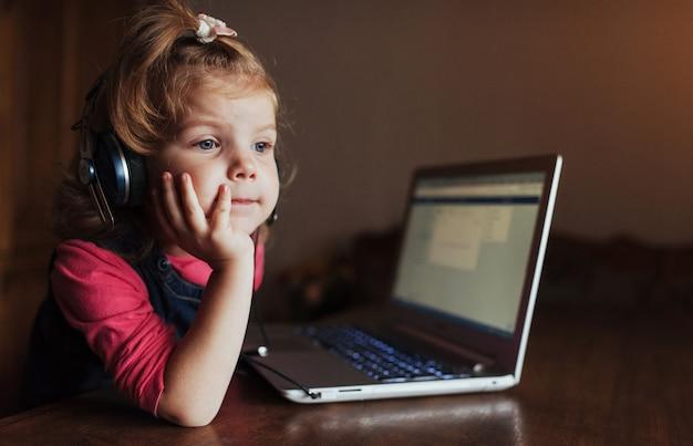 Klein meisje met koptelefoon luisteren naar muziek, met behulp van laptop