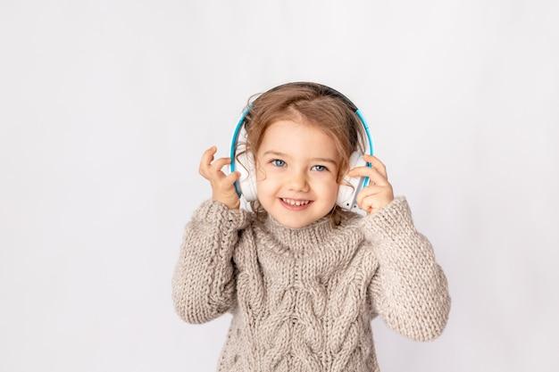 Klein meisje met koptelefoon op een witte achtergrond, luisteren naar muziek en genieten van de ruimte voor tekst