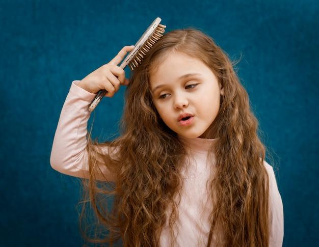 Klein meisje met lang haar wordt gekamd door een kam