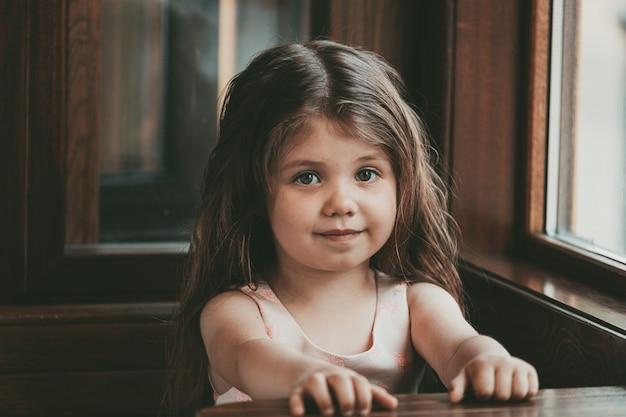 Klein meisje met lang haar zit aan een tafel in een café en glimlacht. hoge kwaliteit foto