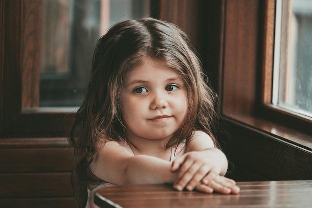 Klein meisje met lang haar zit aan een tafel in een café. hoge kwaliteit foto