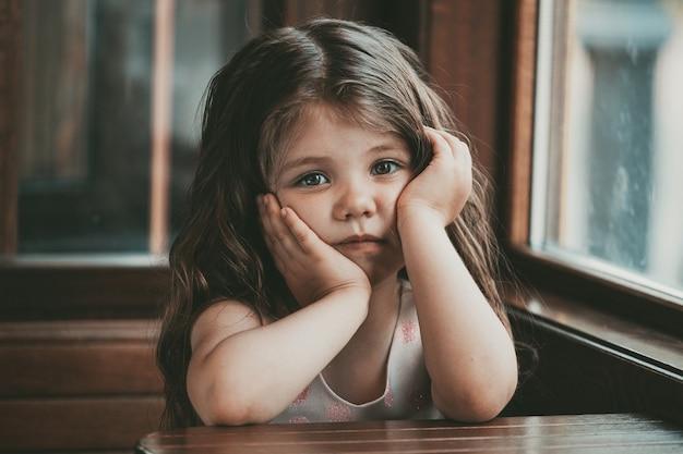 Klein meisje met lang haar zit aan een tafel in een café met een droevig gezicht. hoge kwaliteit foto