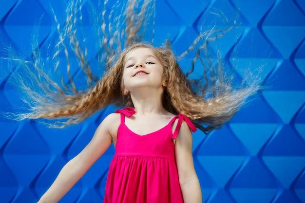 Klein meisje met lang krullend haar in een roze jurk op een blauwe achtergrond danst en lacht, heldere kinderemoties van vreugde, gelukkige jeugd