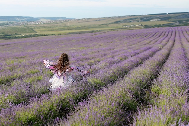 Klein meisje met lange haren die op de lavendel fieldin vlinder jurk lopen.