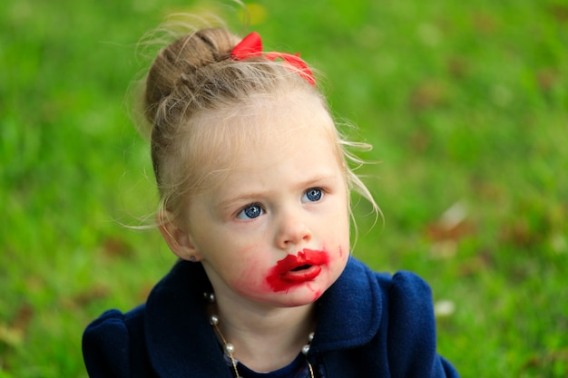 Klein meisje met lippenstift bevlekt gezicht