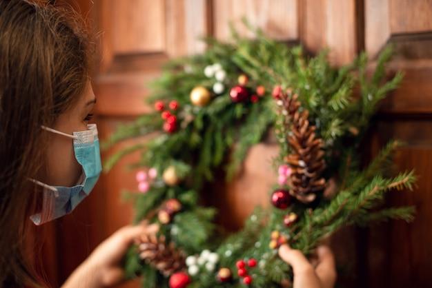 Klein meisje met medisch masker dat kerstkrans aan de toegangsdeur hangt