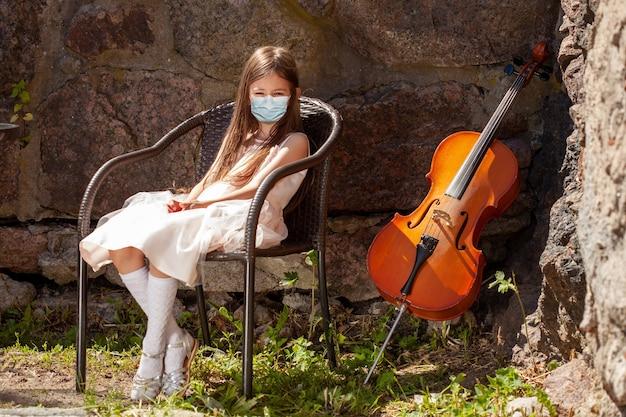 Klein meisje met medisch masker met cello