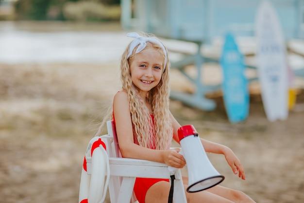Klein meisje met megafoon zittend op het strand met surfplanken op de achtergrond