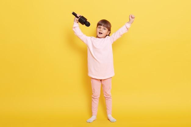 Klein meisje met microfoon zingen tegen gele kleur achtergrond, handen omhoog, regelt concerten, optreden voor iemand, zingt in karaoke, kind met pigtails draagt terloops.