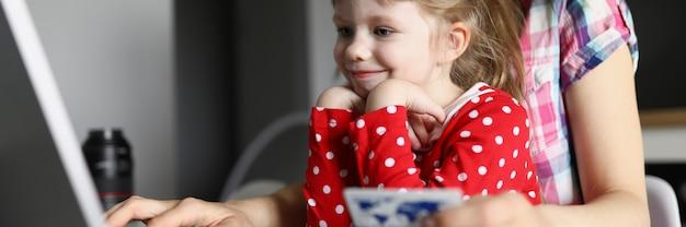 Klein meisje met moeder doet online aankopen via internet