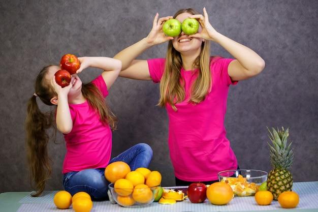 Klein meisje met moeder speelt met fruit en glimlacht. vitaminen en gezonde voeding voor kinderen.