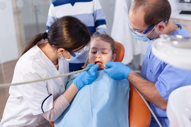 Klein meisje met open mond in de loop van de holtebehandeling zittend op een tandartsstoel. moeder met haar kind in de stomatologiekliniek voor tanden onderzoeken met behulp van moderne instrumenten.