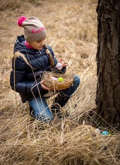 Klein meisje met paaseieren zoeken in het bos