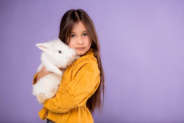 Klein meisje met paashaas op gele achtergrond