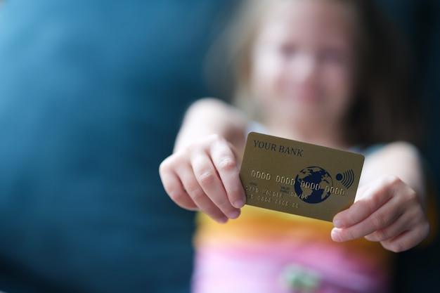 Klein meisje met plastic creditcard in handen close-up