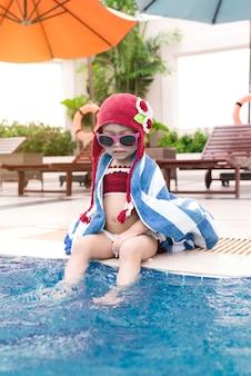 Klein meisje met plezier in het zwembad. zomervakantie en vakantieconcept
