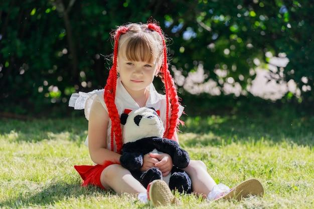 Klein meisje met rode staartjes zit op het gras in het park met een speelgoedbeerpanda. hoge kwaliteit foto