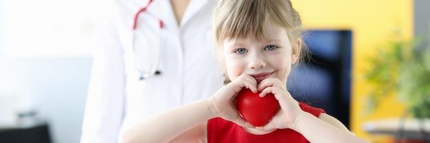 Klein meisje met rood speelgoedhart in haar handen in het gezondheidsconcept van artsenbureau