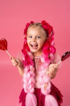 Klein meisje met roze vlechten kanekalon heeft een hartvormige lolly op een roze achtergrond