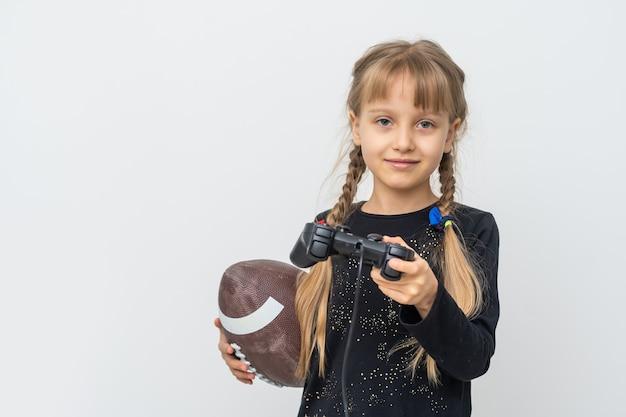 Klein meisje met rugbybal en joystick om thuis videogames te spelen
