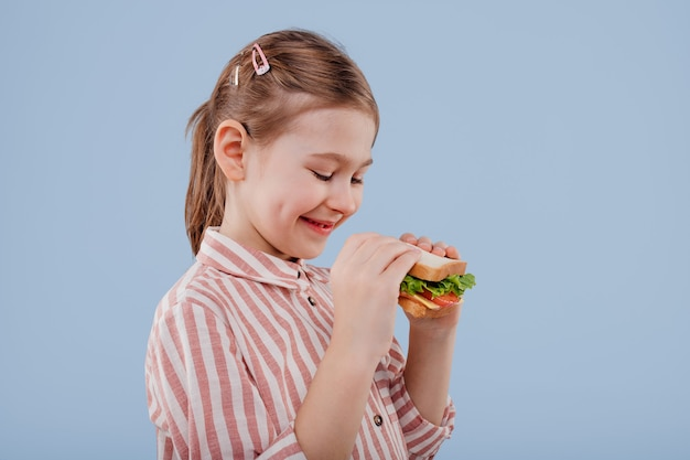 Klein meisje met sandwich in de hand profielweergave geïsoleerd op blauwe achtergrond kopie ruimte