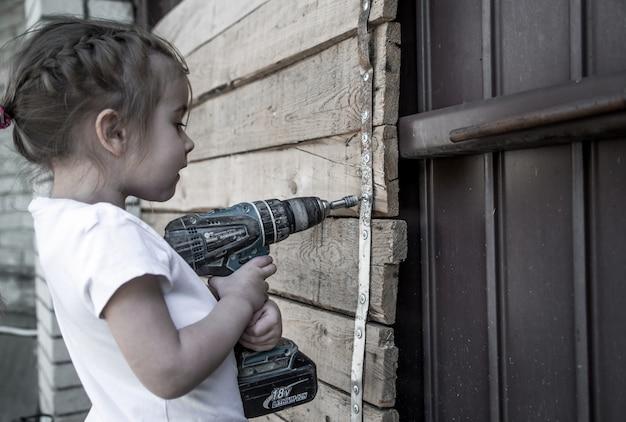 Klein meisje met schroevendraaier in handen