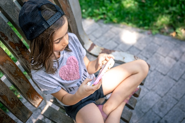 Klein meisje met smartphone in een pet buiten in de zomer.