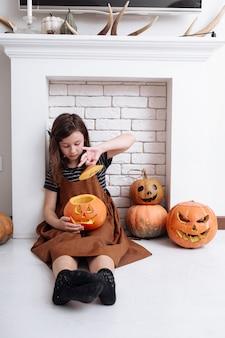Klein meisje met snijwerk pompoen op halloween thuis naast de open haard in de woonkamer. snoep of je leven. kind dat halloween viert.