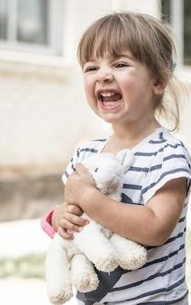 Klein meisje met speelgoed lam