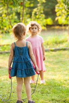 Klein meisje met springtouw in de tuin op een zonnige dag