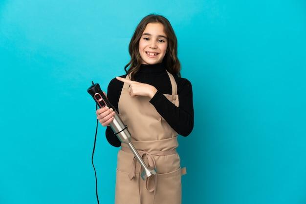 Klein meisje met staafmixer geïsoleerd op blauwe achtergrond wijzend naar de zijkant om een product te presenteren