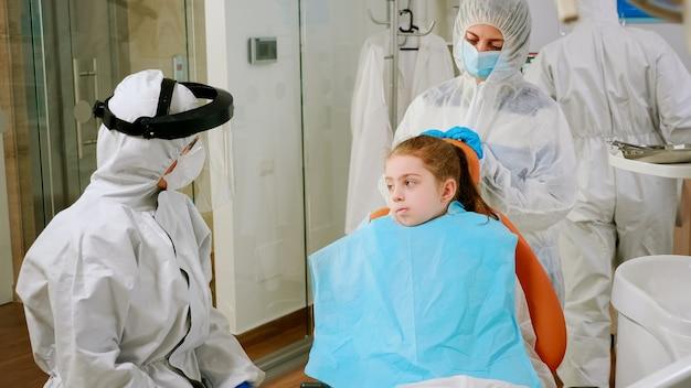 Klein meisje met tandheelkundige slabbetje en ppe-pak luisterende pediatrische tandarts in overall zittend in tandartsstoel tijdens coronaviruspandemie. stomatoloog die een beschermingspak draagt, gezichtsmaskerhandschoenen