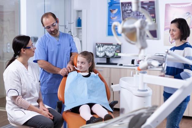 Klein meisje met tandheelkundige slabbetje zittend op een stoel in het kantoor van de tandarts tijdens tand onderzoek. kind met haar moeder tijdens tanden check-up met stomatolog zittend op een stoel.