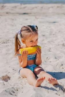 Klein meisje met twee staarten in een zeemeerminzwempak op het zeestrand eet maïs