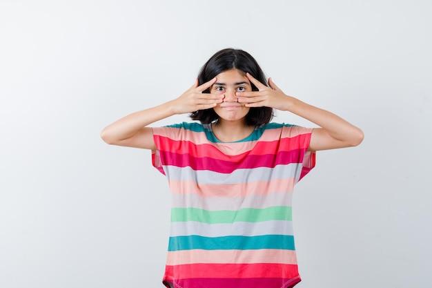 Klein meisje met v-tekens op het oog in een t-shirt, spijkerbroek en ziet er gelukkig uit. vooraanzicht.