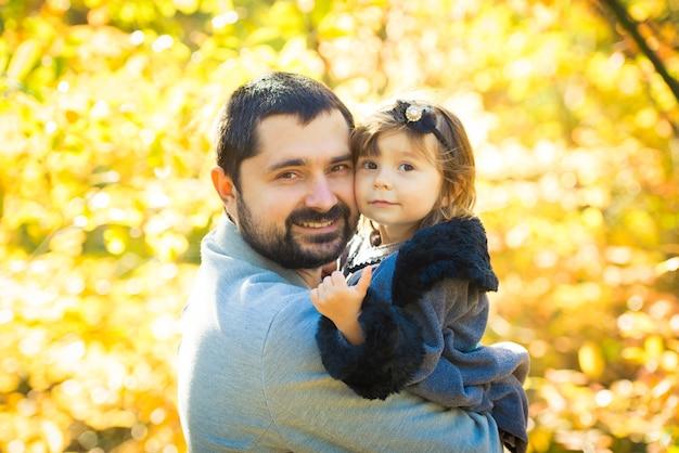 Klein meisje met vader spelen in herfst park.