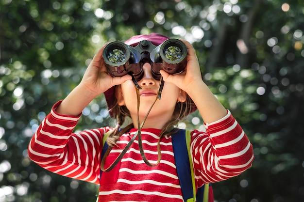 Klein meisje met verrekijker in het bos