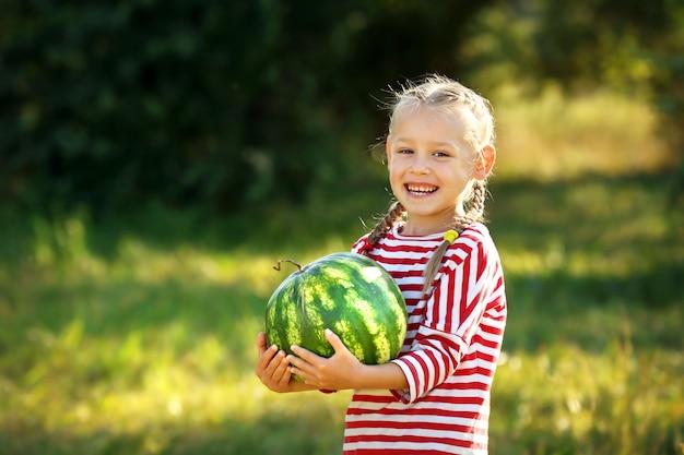 Klein meisje met watermeloen op gazon