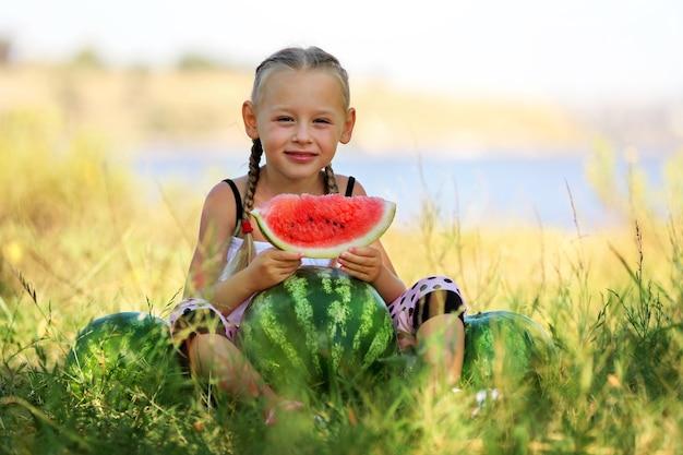 Klein meisje met watermeloenen op gazon