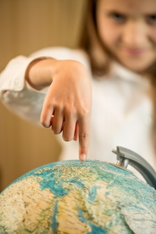 Klein meisje met wijsvinger op earth globe