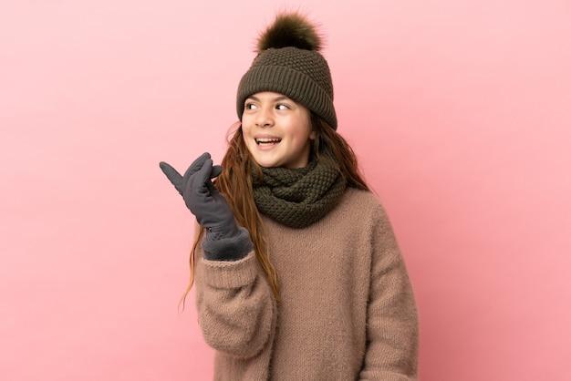 Klein meisje met wintermuts geïsoleerd op roze achtergrond met de bedoeling de oplossing te realiseren terwijl ze een vinger optilt
