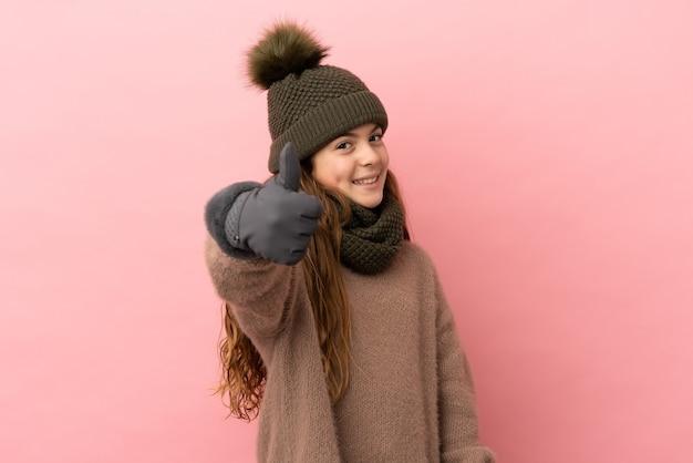Klein meisje met wintermuts geïsoleerd op roze achtergrond met duimen omhoog omdat er iets goeds is gebeurd