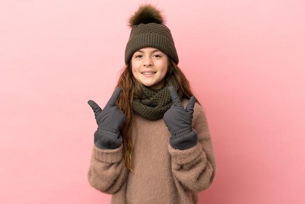 Klein meisje met wintermuts geïsoleerd op roze achtergrond met een duim omhoog gebaar