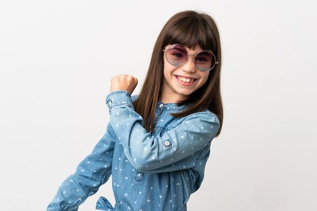 Klein meisje met zonnebril geïsoleerd op een witte achtergrond die een overwinning viert