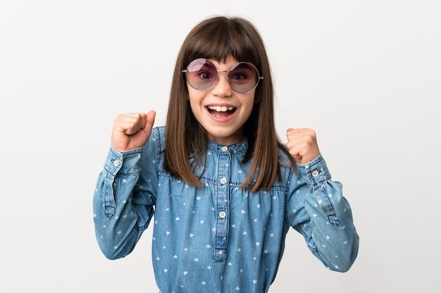 Klein meisje met zonnebril geïsoleerd op een witte achtergrond vieren een overwinning in winnaar positie