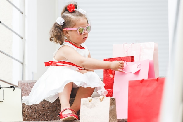 Klein meisje met zonnebril zit op de trappen in het winkelcentrum met gekleurde tassen