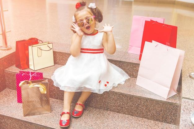 Klein meisje met zonnebril zit op de trappen in het winkelcentrum met winkelen