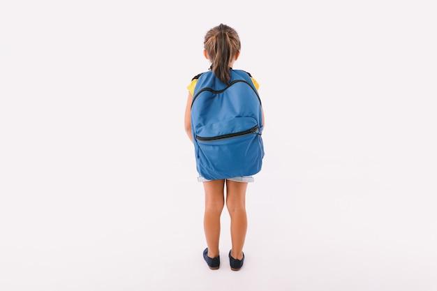 Klein meisje met zwart haar gekleed in denim overalls en een blauw t-shirt, met een rugzak klaar om terug te gaan naar school, met haar rug gedraaid, op witte achtergrond